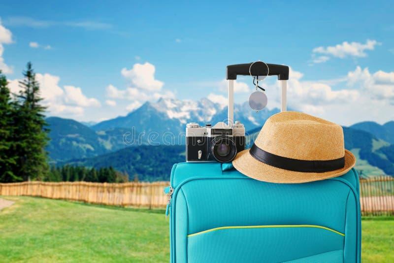 旅客行李、照相机和浅顶软呢帽帽子的休闲图象在一个农村风景前面 E 免版税库存图片