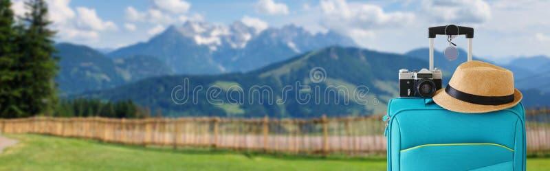 旅客行李、照相机和浅顶软呢帽帽子的休闲图象 一个农村风景的前面 E ?? 库存照片