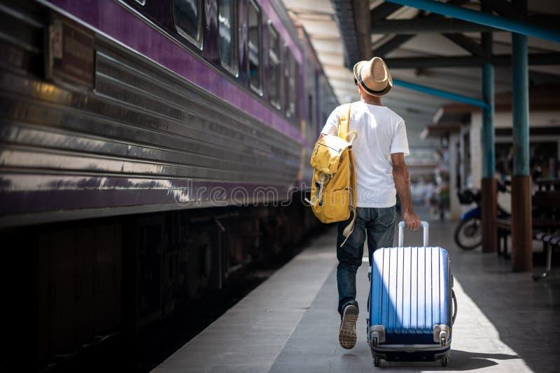 旅客走和等待训练在火车站 免版税库存图片