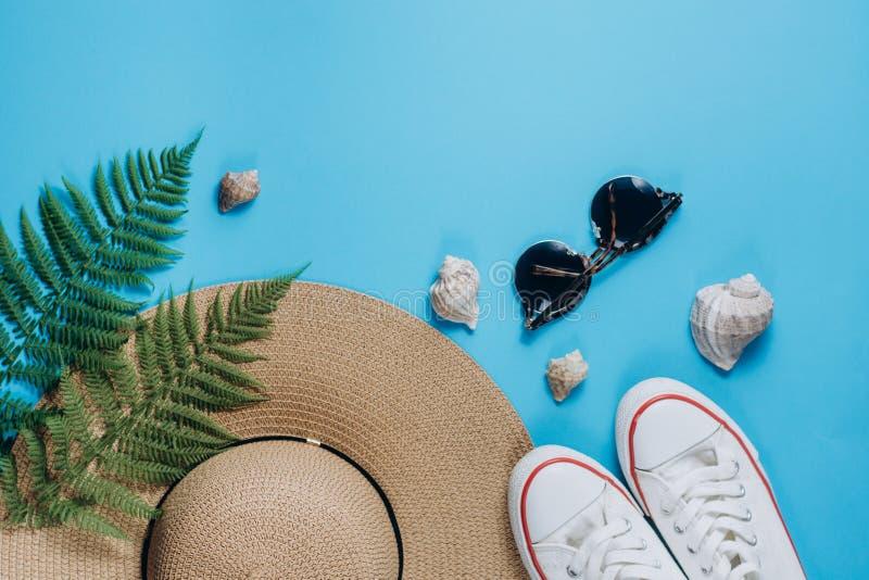 旅客辅助部件、热带蕨叶子分支、帽子、太阳镜、鞋类和贝壳在蓝色背景 库存图片