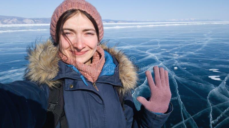 旅客采取selfie并且摇她的手在她的智能手机照相机  在一次旅行期间的微笑的女孩到冬天贝加尔湖 库存照片