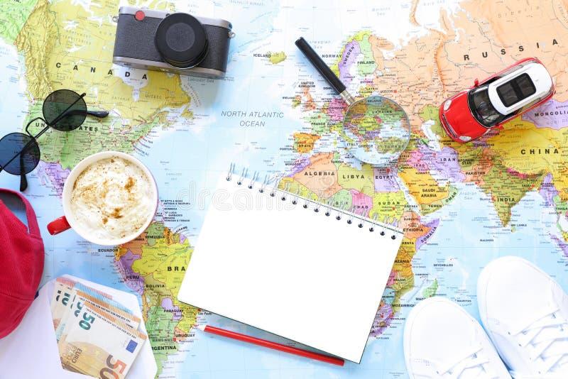 旅客` s辅助部件和项目与拷贝空间在世界地图背景,旅行由汽车概念 免版税图库摄影