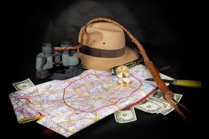 旅游业和冒险概念 在城市地图的指南针与手电、浅顶软呢帽帽子, bullwhip,双眼,刀子和美金在dar 免版税图库摄影
