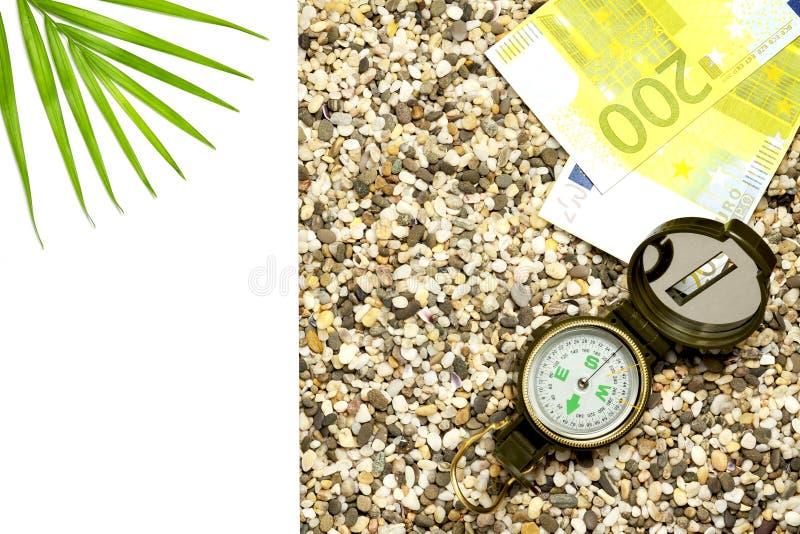 旅游业的概念 有欧元谎言的指南针在沙子,到左边是文本孤立的一个地方 库存图片