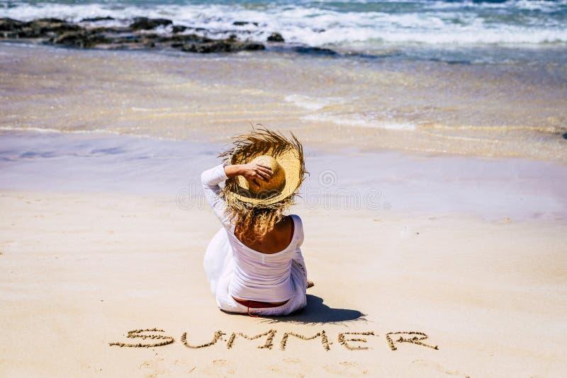 旅游人员和夏日海滩概念-户外度假休闲活动-戴帽子和白色连衣裙的女性 免版税库存照片