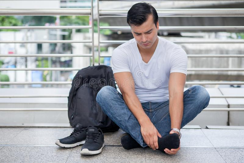旅游人坐地板离开按摩脚的鞋子走很多脚痛苦在长的步行以后 库存图片