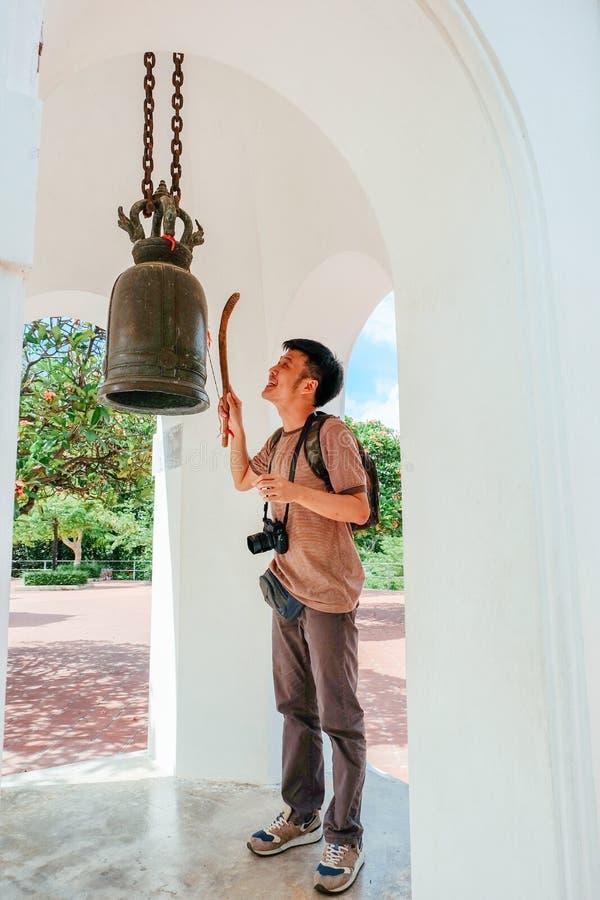 旅游人敲在泰国寺庙的金属响铃 免版税图库摄影