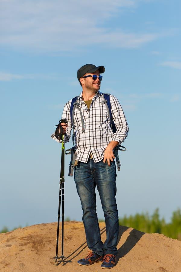 旅游人照片太阳镜的用走的棍子在小山 免版税库存照片