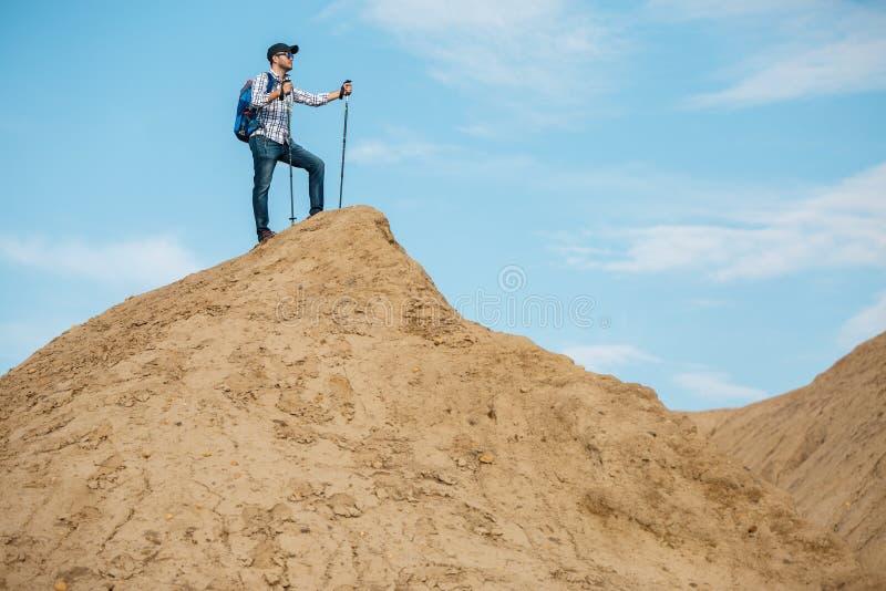 旅游人照片有背包和棍子的走的向前在小山 免版税库存照片