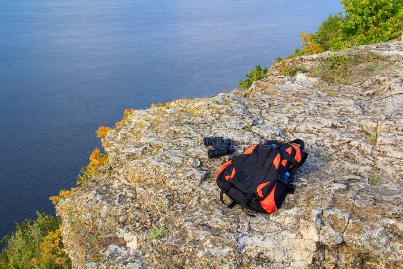 旅游双眼和在岩石的旅游背包谎言在反对一条蓝色河的山顶部 免版税图库摄影