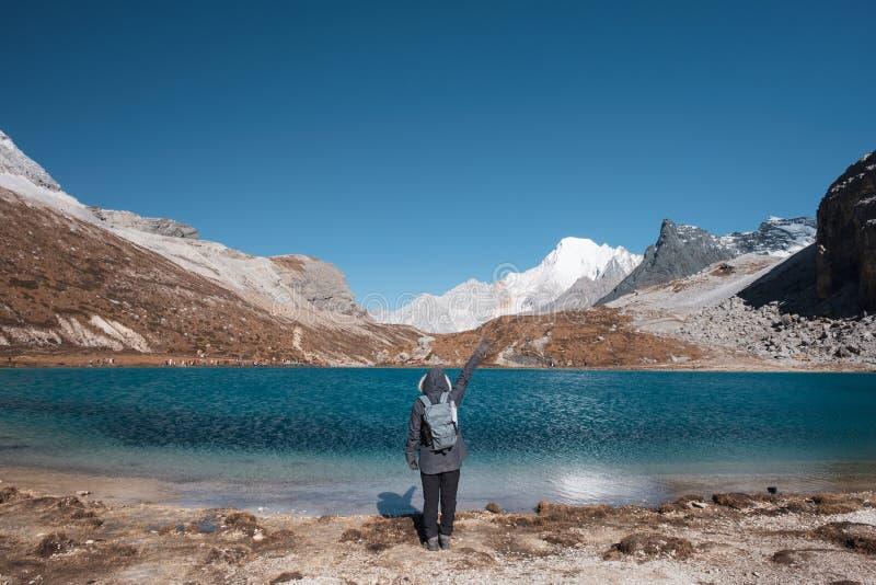 旅游培养手与绿松石湖和山脉在峰顶 图库摄影