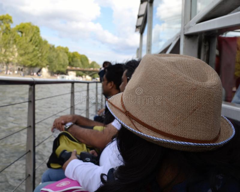 旅游夫人佩带的妇女的秸杆浅顶软呢帽帽子,在Siene河的巡航游览 库存图片