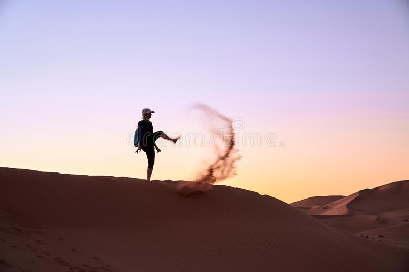 旅游女孩在撒哈拉大沙漠在天空中踢沙子 免版税库存图片