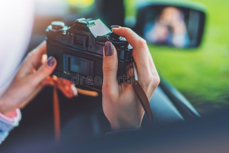 旅游女孩在采取摄影的一辆自动汽车的一个开窗口里在减速火箭的葡萄酒照片照相机庄稼,摄影师看点击 库存照片