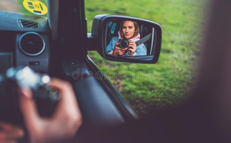 旅游女孩在采取摄影的汽车的一个开窗口里在减速火箭的葡萄酒照片照相机,看在反射的摄影师点击 免版税图库摄影