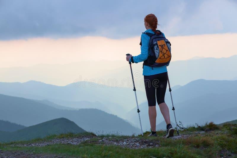 旅游女孩用后面大袋和跟踪棍子在草坪停留 美丽的天空 太阳光芒在山倒下 库存照片
