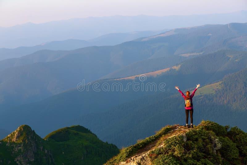 旅游女孩用跟踪的棍子和后面大袋在峭壁的边缘 与高山的风景 免版税库存图片