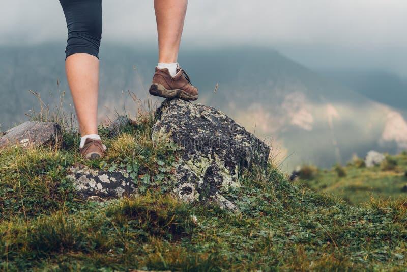 旅游女孩的腿在岩石站立 妇女远足者享用Th 库存图片