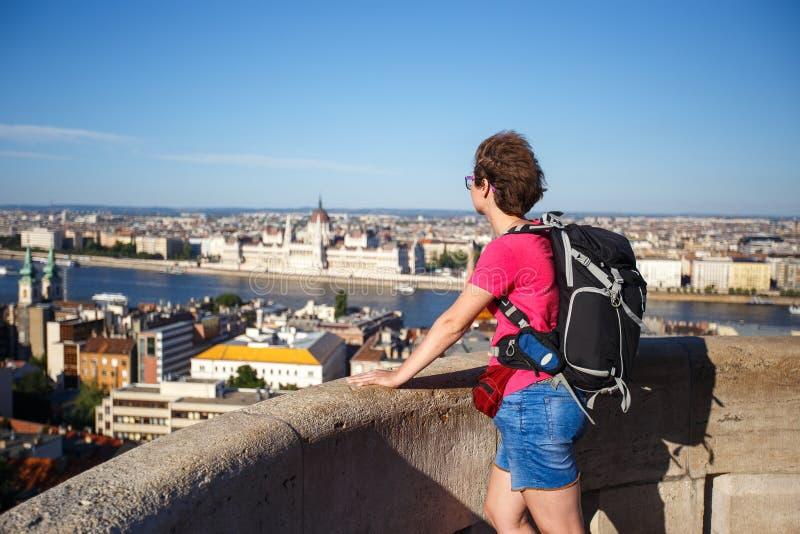 旅游女孩站立与她在观察台在忽略议会的高度在匈牙利,布达佩斯c 免版税图库摄影