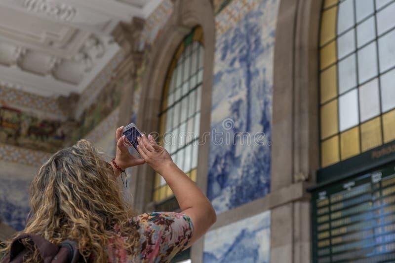 旅游妇女在城市拍与她的手机的一张照片从圣本托火车站的历史内部, 库存图片