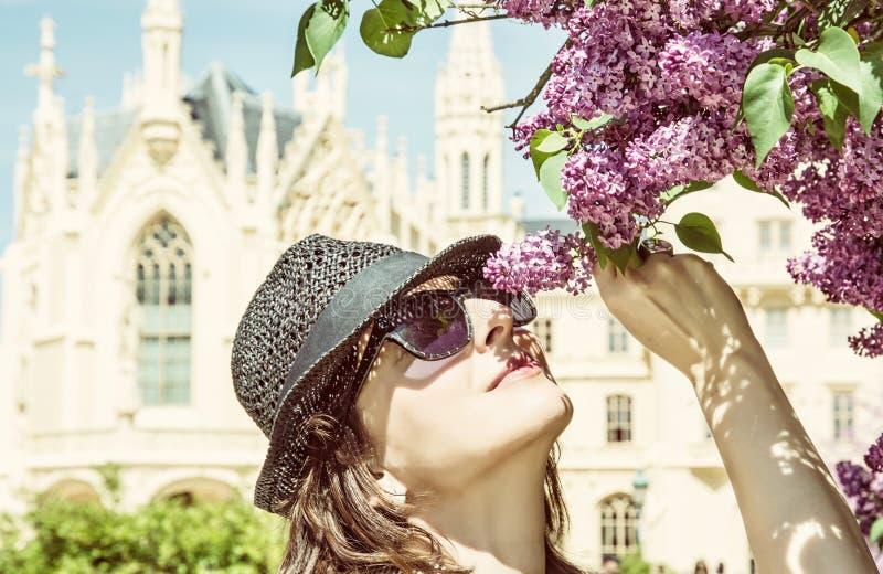 旅游妇女在Lednice城堡,黄色附近嗅开花的树 免版税图库摄影