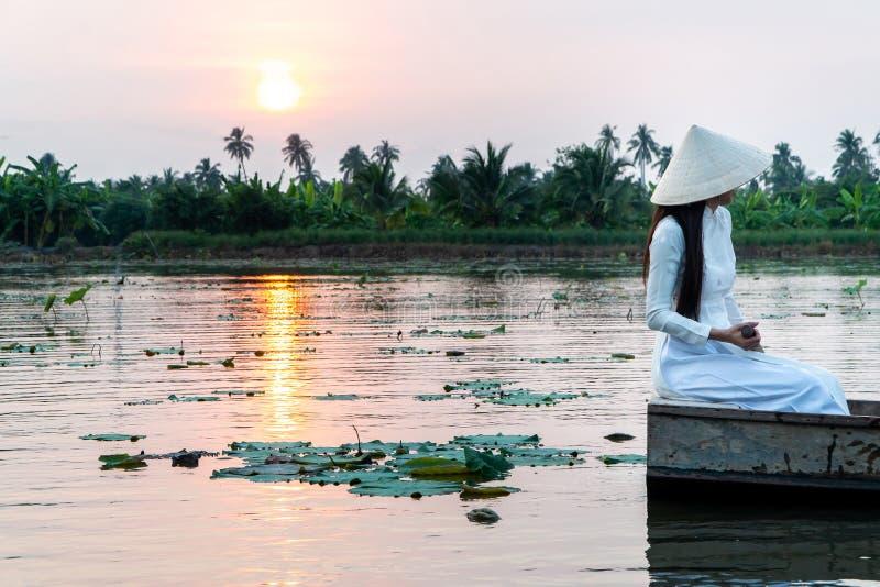 旅游妇女戴白色传统越南礼服Ao Wai和越南农夫的帽子和坐在花的木小船 库存图片
