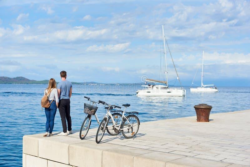 旅游对、男人和妇女有自行车的在上流在海水附近铺了石边路在晴天 免版税库存照片