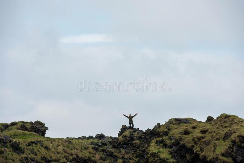 旅游摆在Londrangar玄武岩峭壁,冰岛 库存图片