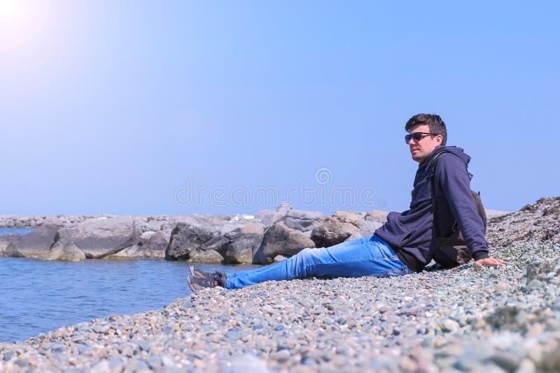 旅游旅行家来向海滩扔石头的人坐并且看海 库存照片