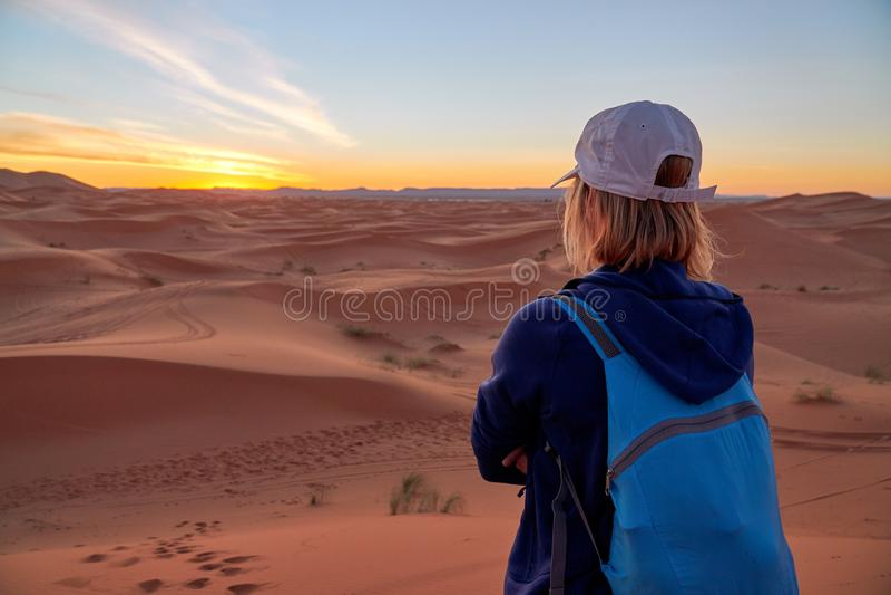 旅游背包徒步旅行者女孩从观看的日落的后面在沙漠 免版税库存照片
