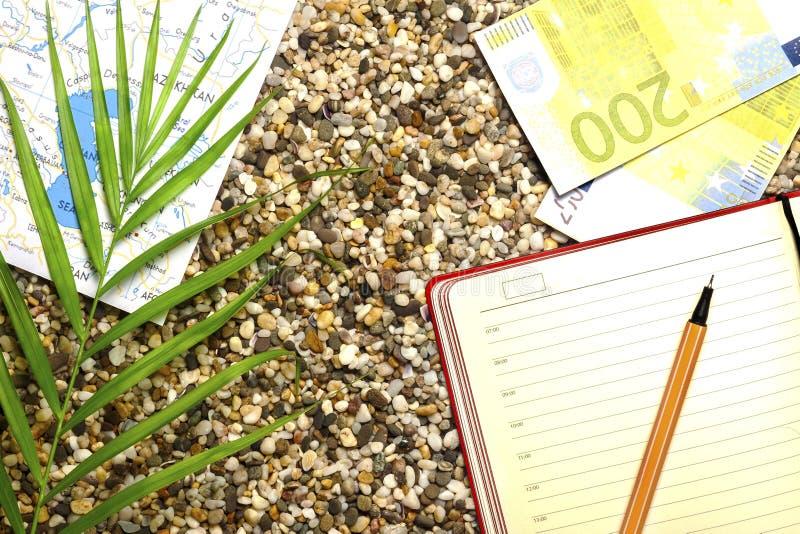 旅游题材,沙滩,指南针,金钱,有钢笔植物的笔记本 图库摄影