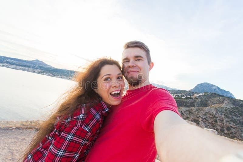 旅行、假期和假日概念-获得美好的夫妇乐趣,采取在美好的风景的selfie 库存图片