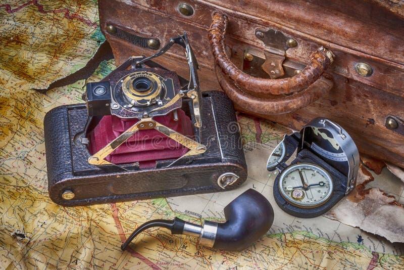 旅行、冒险、探险与照相机折叠的葡萄酒,老手提箱、指南针和地图与烟斗 皇族释放例证