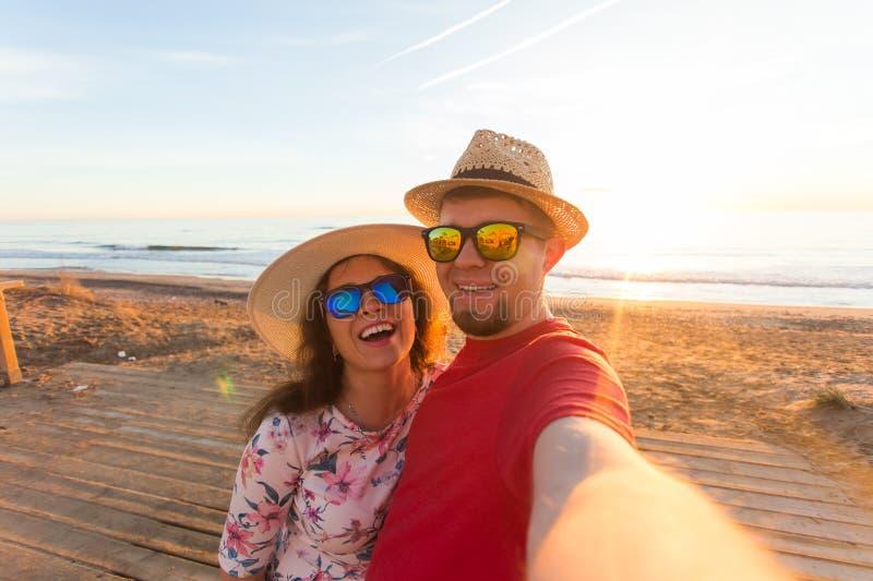 旅行、夏天和假日概念-采取在海滩的可爱的夫妇selfie 库存照片