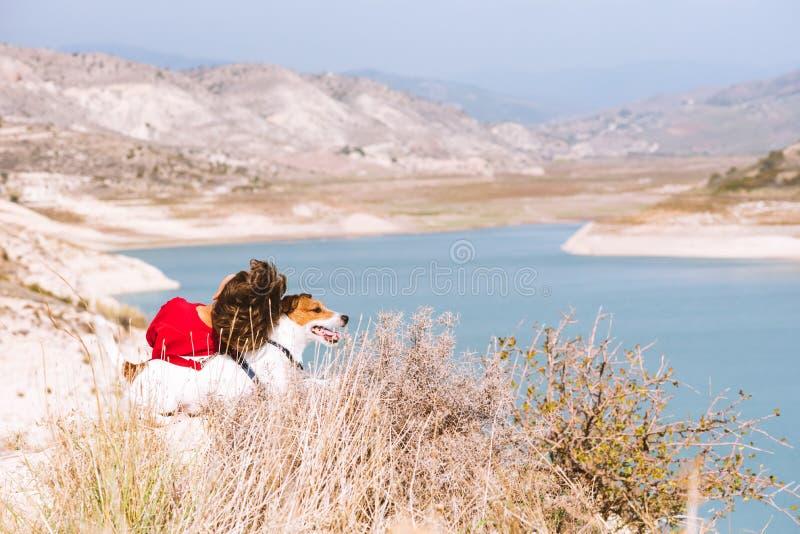 旅行、家庭和家庭生活概念—放松在山顶部的孩子和他的爱犬看美好的谷视图 免版税库存照片