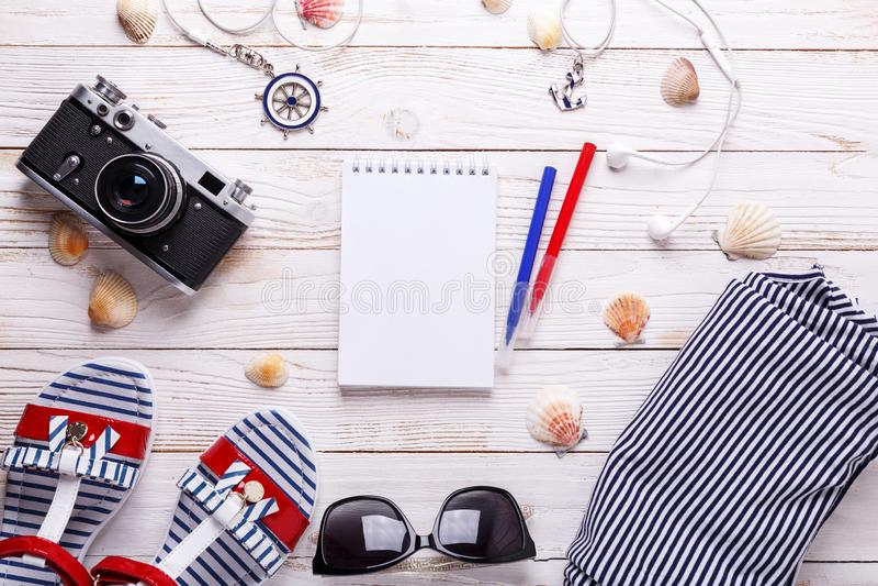 旅行与凉鞋、耳机、太阳镜、照相机、贝壳、笔记本和镶边T恤杉的假期概念 库存照片