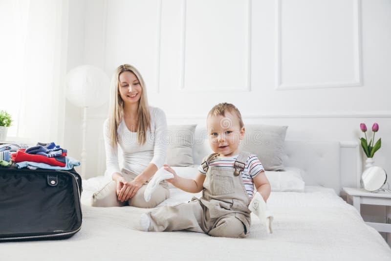 旅行与孩子 有她的儿童包装的愉快的母亲在假日穿衣 库存照片
