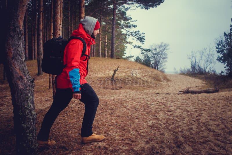 一个人背包旅行_旅行与背包的一件红色夹克的一个人