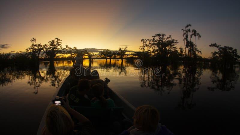 旅行乘在一个盐水湖的独木舟的游人在亚马逊,当拍日落照片时 免版税库存图片