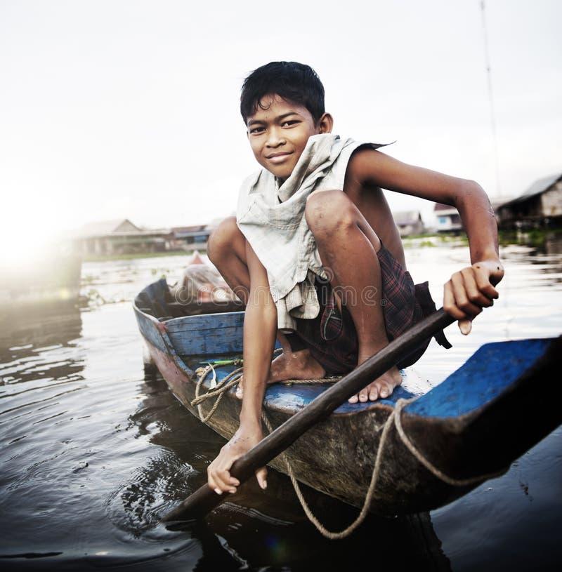 旅行乘在浮动村庄概念的小船的男孩 库存照片