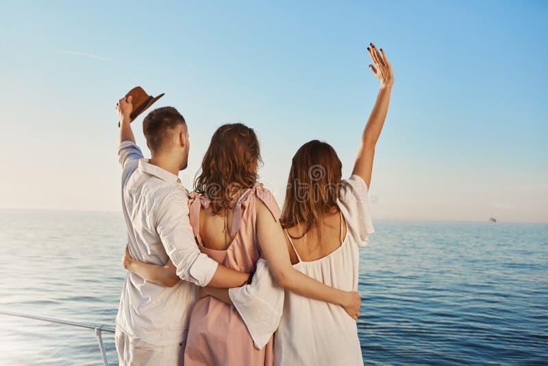 旅行乘小船的后面观点的三个最好的朋友拥抱和挥动,当看海时 是在豪华的人们 免版税库存照片