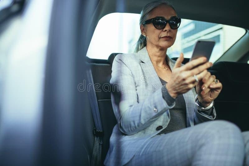 旅行乘汽车的资深女实业家使用巧妙的电话 库存照片