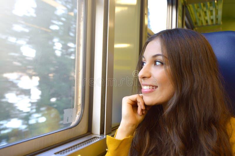 旅行乘火车的微笑的少妇 坐在tr的愉快的女孩 免版税库存图片