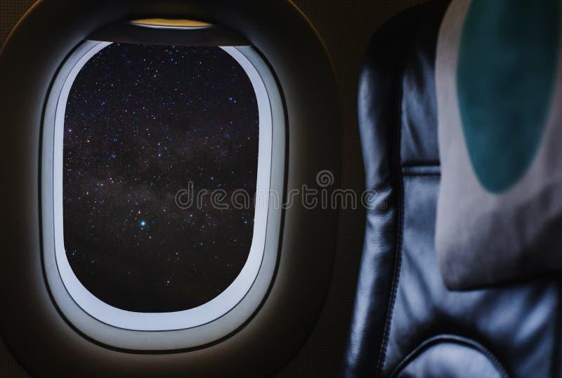 旅行乘空中飞机,看通过充分享用美丽的夜空星和银河的平面窗口 库存图片
