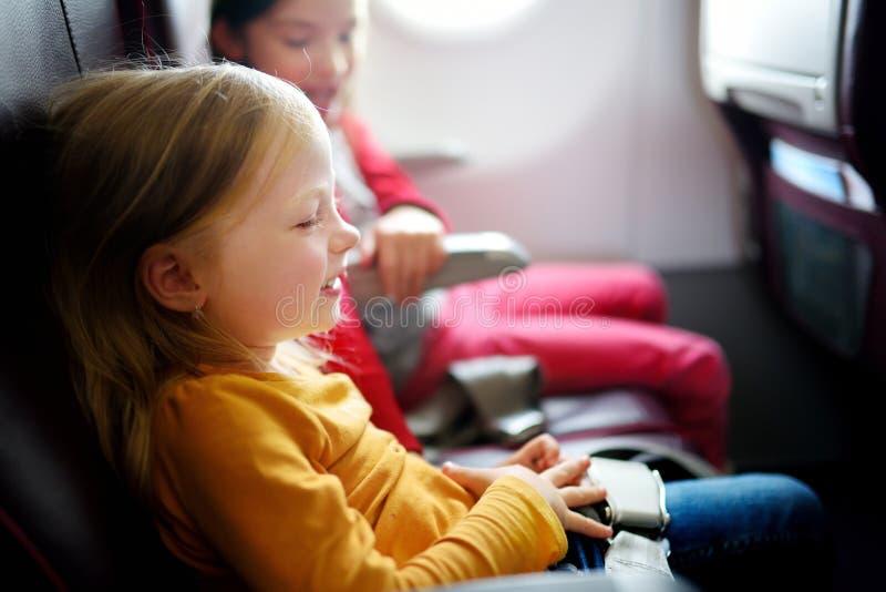 旅行乘飞机的两个可爱的小女孩 看的孩子坐由航空器窗口和外面 免版税库存照片