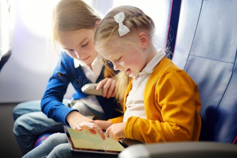 旅行乘飞机的可爱的小女孩 坐由航空器窗口和使用一种数字式片剂的孩子在飞行期间 免版税库存图片