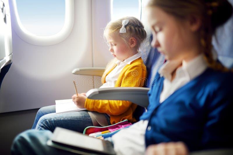 旅行乘飞机的可爱的小女孩 坐由航空器窗口和画与五颜六色的铅笔的孩子一张图片 免版税库存图片