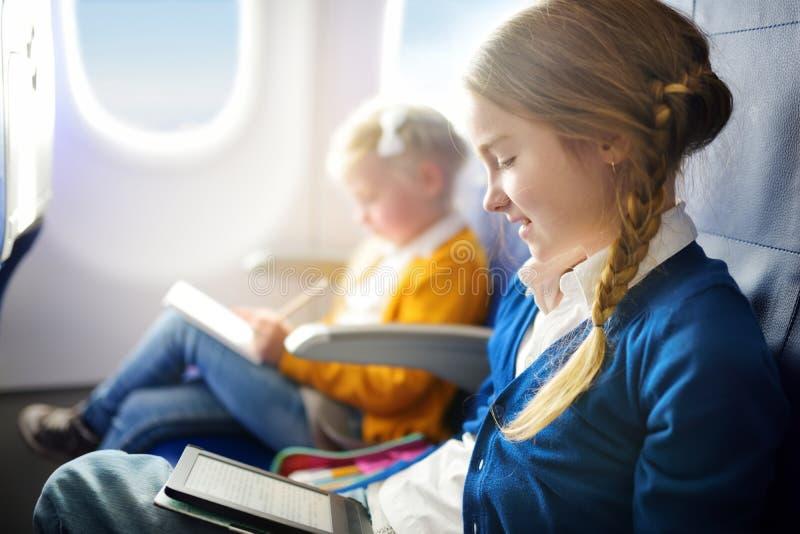 旅行乘飞机的可爱的小孩 坐由航空器窗口和读她的ebook的女孩在飞行期间 库存照片
