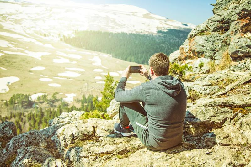 旅行人坐在山顶部并且为从旅游旅客的后面的智能手机视图照相  库存图片