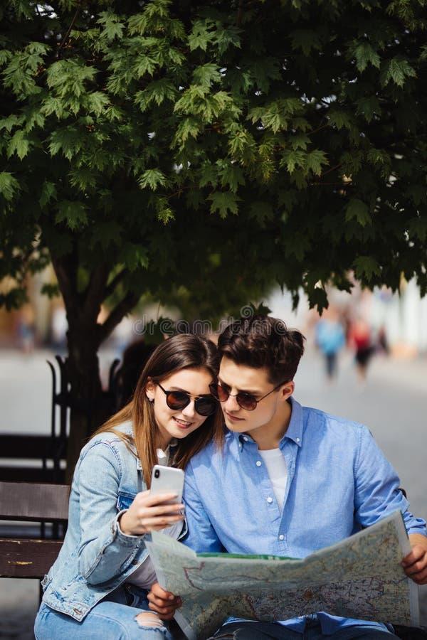 旅行使用地图和电话的美好的旅游夫妇 站立在街道上的微笑的男人和少妇画象,搜寻Dest 库存照片